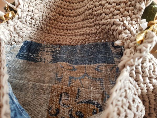 Detalle del interior del bolso forrado con tela de loneta, a tonos azulados y tostados.