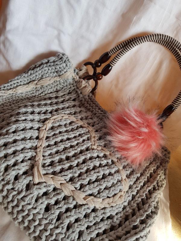 Detalle de las asas del bolso y la aplicación de pompón salmón