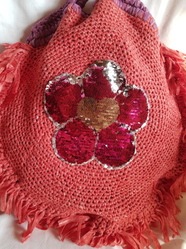 Detalle de flor del bolso de hilo de algodón salmón, forrado con tela de loneta y aplicaciones de flor y buho de paillette.
