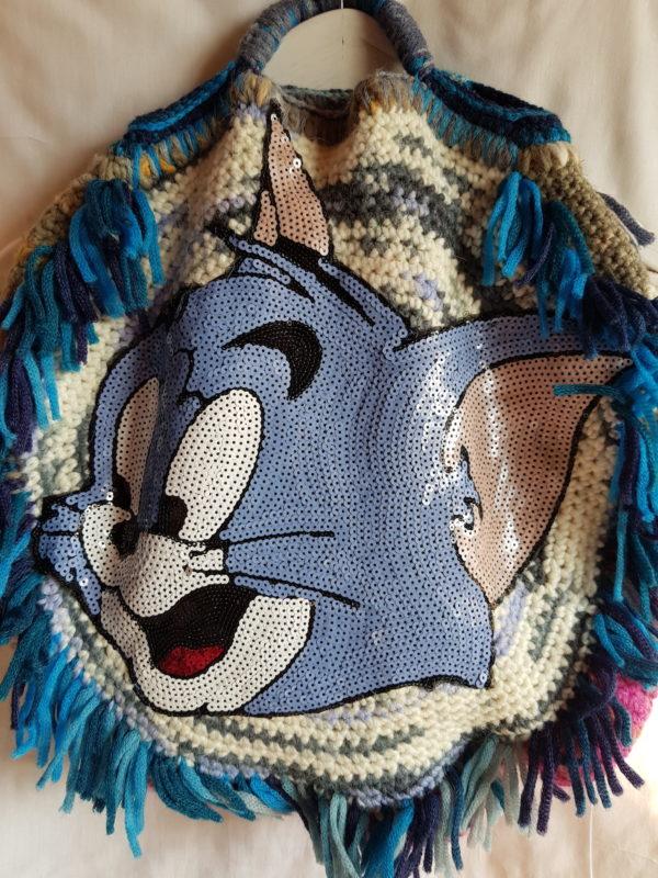 Detalle del bolso de lana combinación de tonos azules y tostado claro, forrado de tela de loneta , flecos de la misma lana y aplicación de gato de paillete.