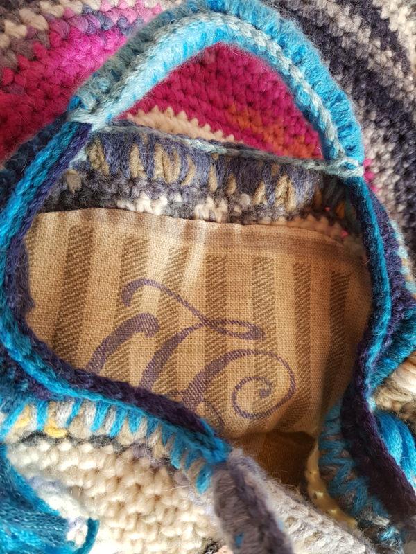 Detalle del interior del bolso de loneta de tonos ocres con letras y bolsillo