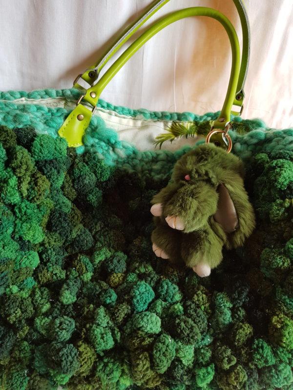 etalle del bolso de lana bucle, combinación de tonalidades verdes, forrado con tela de loneta y detalle de conejo piel sintética, asas de color verde de piel.