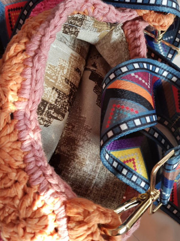 Detalle del interior del bolso forrado de tela de loneta con motivos geometricos. asa de tela satinada.