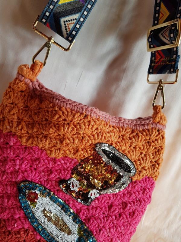 Detalle del asa de colores de tela satinada del bolso de crochet de combinaciones de colores, forrado con tela de loneta, y aplicaciones de plarto y taza de paillete
