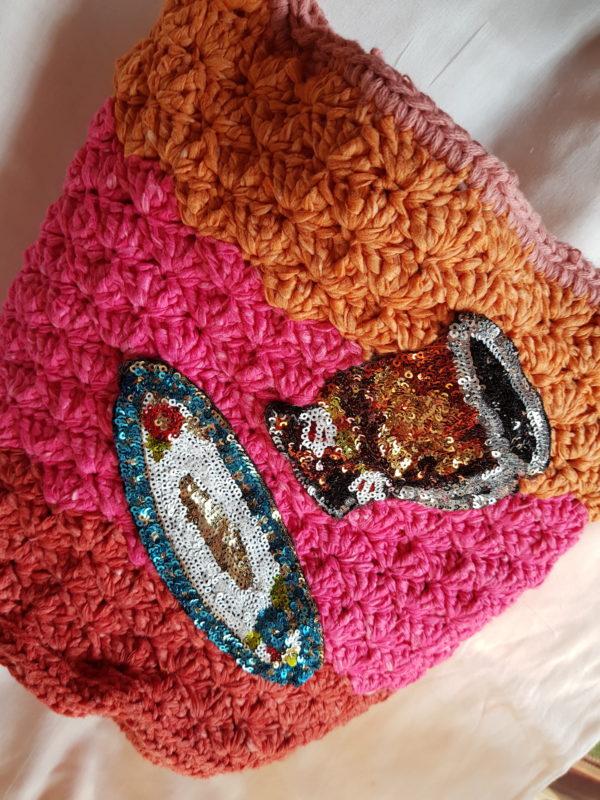 Bolso de crochet de combinaciones de colores, forrado con tela de loneta, y aplicaciones de plarto y taza de paillete