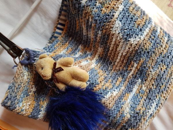 Detalle del bolso hecho a mano con hilo de algodón de mezcla de colores azules y tostados, forrado con tela de loneta rallada y complemento decorativo de oso con pompón azul, asas de piel