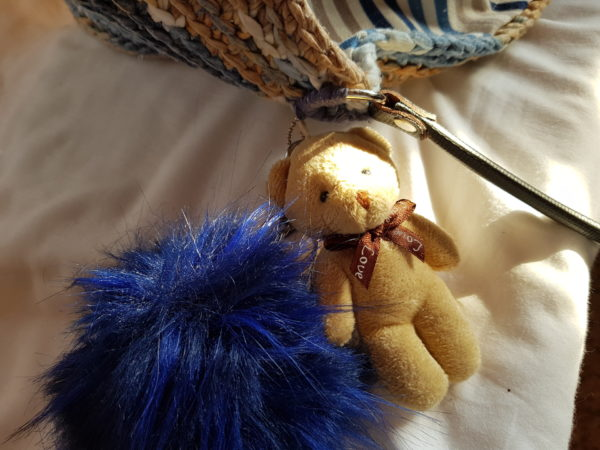 Bolso hecho a mano con hilo de algodón de mezcla de colores azules y tostados, forrado con tela de loneta rallada y complemento decorativo de oso con pompón azul, asas de piel