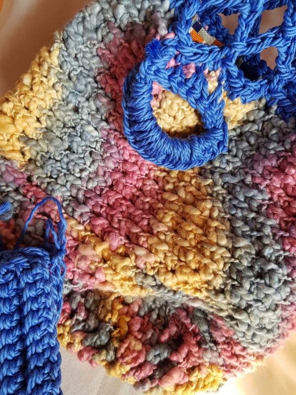 Detalle del bolso de crochet tejido a punto de red, combinación de colores, forrado por la parte superior con tela estampada y bolso de mano de conjunto