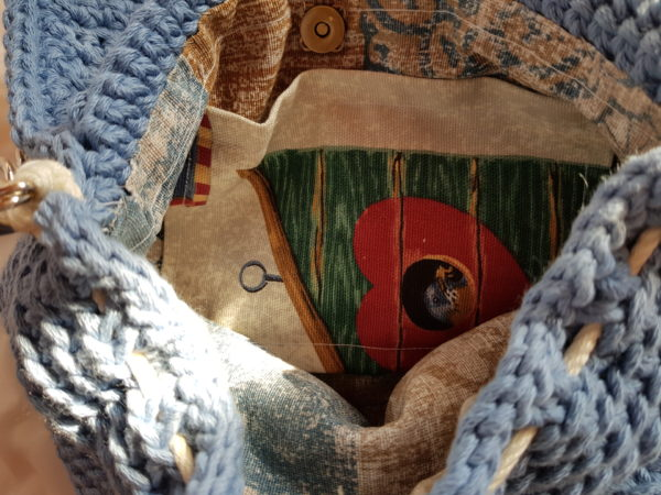 Detalle del interior del bolso hecho a mano con hilo de algodón con detalle de paillette., tela de loneta motivos jaulas de pajaros