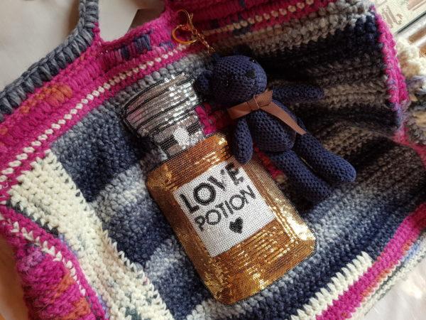 Detalle del otro lado del bolso de crochet con lana de mezcla combinación de colores, forro de tela de loneta con aplicaciones y oso azul marino