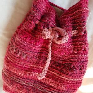 Detalle de la bolsa de crochet de colores fucsia combinado, forrada con tela de loneta
