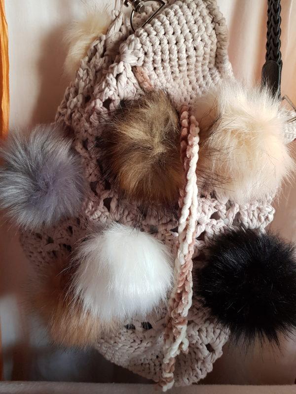 Detalle de la bolsa grande de crochet con hilo de algodon, forrada con tela dd loneta y 10 pompones de colores naturales con asa de terciopelo